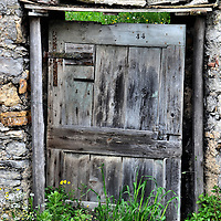Old Crooked Wooden Storage Door in Le Grazie, Italy <br /> Driving through Italy&rsquo;s northern coast is an adventure to say the least.  You are either speeding along the motorways as they plunge in and out of tunnels, or you are slowly trying to navigate the twisting, narrow roads that hug the hilly shores.  Either way, it is hard to drink in the beautiful scenery when you are concentrating on every turn.  But every once in a while you spot something that&rsquo;s charming in its simplicity.  An example is this old, crooked door that appears to lead to abandoned roadside storage.