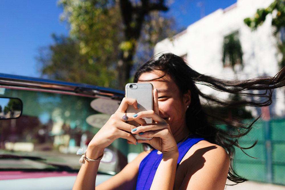 20 something takes photos with her cell phone on a convertible tour of Old Havana in Havana, Cuba