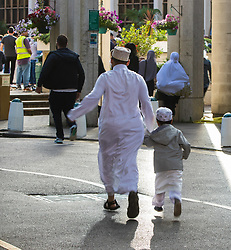 London, June 25th 2017. Dawn breaks over the London Central Mosque in Regent's Park as Muslims celebrate Eid ul-Fitr Day. PICTURED: Running late, a man and boy rush into the Mosque.