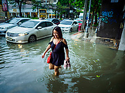 27 MAY 2017 - BANGKOK, THAILAND: A woman walks on a sidewalk flooded by monsoonal rains along Ekkamai Road in suburban Bangkok. The rainy season in Bangkok usually starts in mid-June but started almost a month early this year. There have been daily thunderstorms and localized flooding throughout central Thailand since the middle of May.     PHOTO BY JACK KURTZ