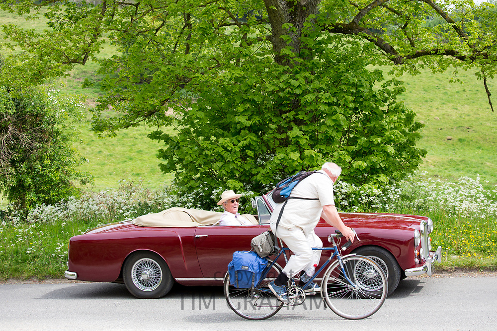 Driver in Alvis classic car chats with cyclist along a country lane in The Cotswolds, England
