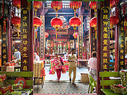06 JUNE 2015 - KUALA LUMPUR, MALAYSIA:  People walk out of the Sin Ze Si Ze temple in Kuala Lumpur. It is the oldest Taoist temple in KL. It's named after patron deities Sin Sze Ya and Si Sze Ya, real people who were heros for fighting against Malay natives in the early days of Kuala Lumpur.  PHOTO BY JACK KURTZ