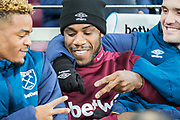 Michail Antonio (West Ham) playing 'Rock, paper, scissors' with Grady Diangana (West Ham) looked on by Lucas Perez (West Ham) on the bench prior to the Premier League match between West Ham United and Brighton and Hove Albion at the London Stadium, London, England on 2 January 2019.