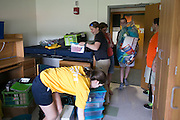 Cassidy Clayton of Leesburg, Florida, center, moves into her room in Susan B. Anthony Hall on move-in day for new students at the University of Rochester on Tuesday, August 25, 2015.