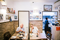 "NAPLES, ITALY - 12 SEPTEMBER 2018: (R-L) Giusy Aiese, her father Gaetano and a customer are seen here at the Taverna del Buongustaio, a tavern in Naples, Italy, on September 12th 2018.<br /> <br /> Taverna del Buongustaio was founded in the 1930s by wine producer of the province of Caserta. Gaetano Aiese and his daughter Giusy have been managing the tavern since 1996. Customers of the Taverna are professors of the nearby University, students, merchants and employees of via Toledo, the commercial street right around the corner. Giusy and her father Gaetano decided to invest in the traditional Neapolitan cuisine. ""I learned cooking from my dad. And my dad learned cooking from his mother"", Giusy said."