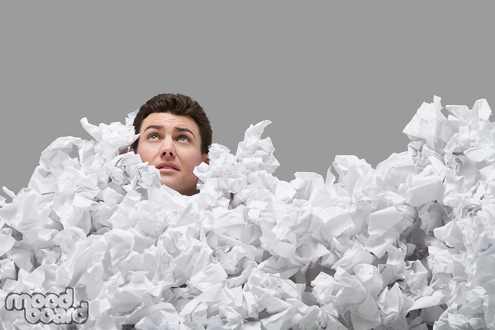 Adult man covered in crumpled paper looking up