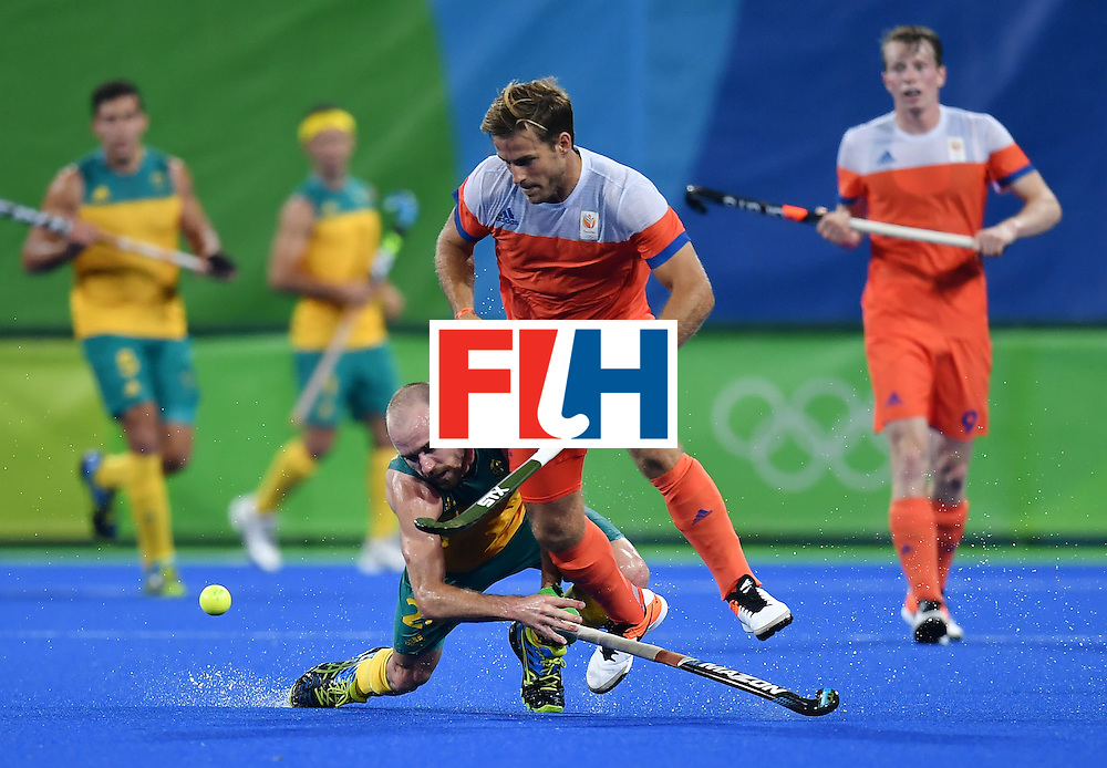 Australia's Matthew Swann (L) vies with Netherland's Jeroen Hertzberger during the men's quarterfinal field hockey Netherlands vs Australia match of the Rio 2016 Olympics Games at the Olympic Hockey Centre in Rio de Janeiro on August 14, 2016. / AFP / MANAN VATSYAYANA        (Photo credit should read MANAN VATSYAYANA/AFP/Getty Images)
