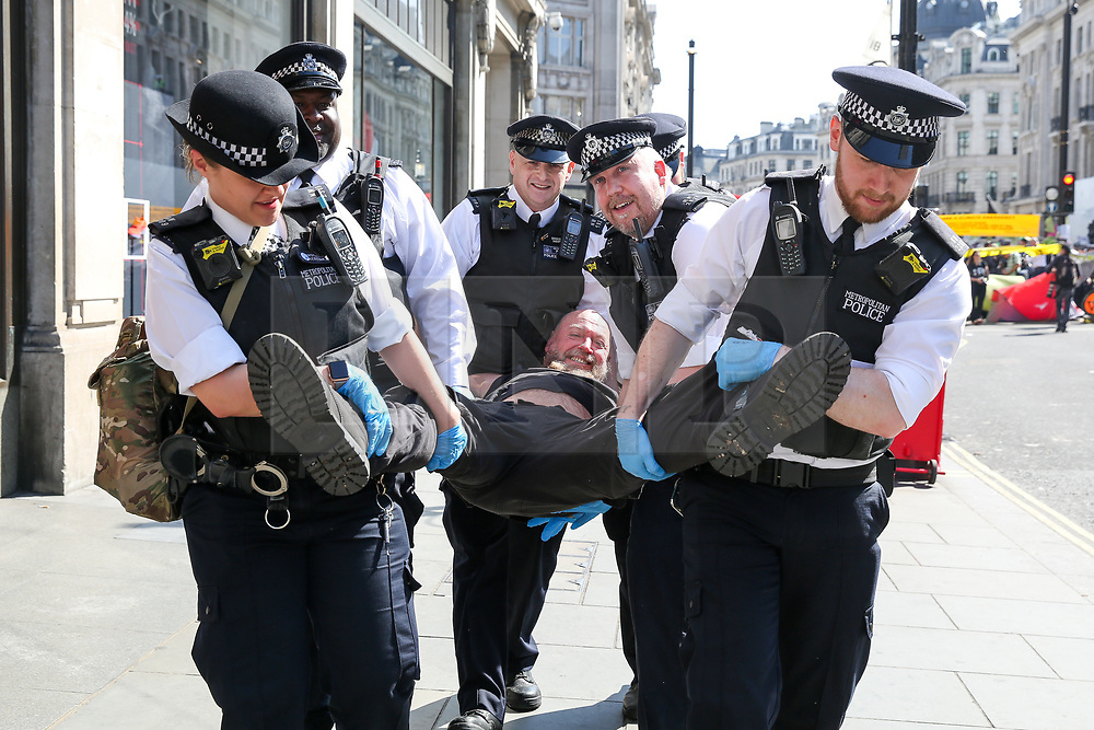 © Licensed to London News Pictures. 19/04/2019. London, UK. An environmental activist is detained by the police in Oxford Circus on the fifth day of the climate change protest by the Extinction Rebellion movement group. A large number of police presence around the pink boat as they begin to un-bonding the activist who have glued themselves. Photo credit: Dinendra Haria/LNP
