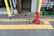 pedestrian sidewalk with red traffic cone and old loose Tactile Ground Surface Indicators tiles for the blind Japan