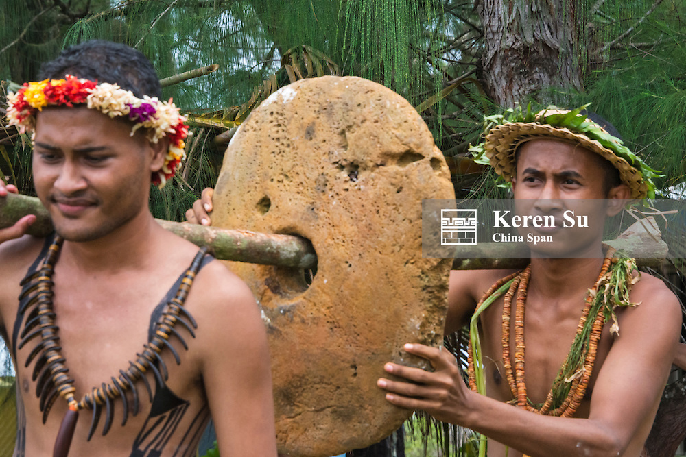 Yapase men in traditional clothing carrying stone money at Yap Day Festival, Yap Island, Federated States of Micronesia