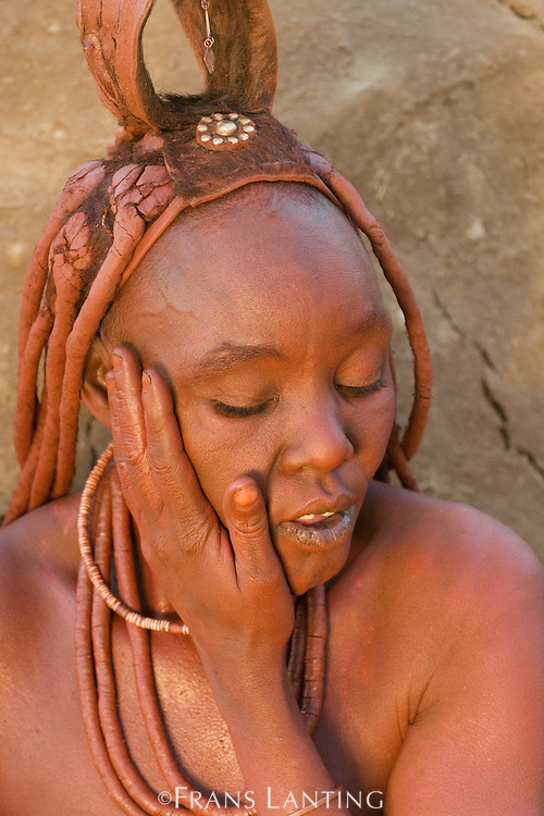 Himba woman applying perfume plant balm to skin, Puros Conservancy, Damaraland, Namibia