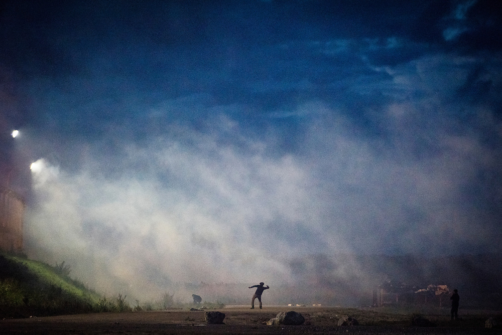 Amid teargas, a refugee throws a rock towards a fence protecting the highway approaching the port of Calais at The Jungle refugee camp on October 22, 2016 in Calais, France. The operation to dismantle the camp would begin two days later.