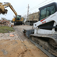 Tupelo Public Works removes what's left of a house along Fair Oaks Drive Tuesday that had to be torn down following last weeks tornado.