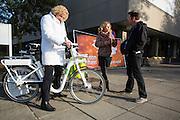 Met interesse kijkt een vrouw naar de Gobike, de elektrische deelfiets die als eerste op bedrijventerrein Lage Weide in Utrecht wordt geplaatst. In Utrecht wordt voor het kantoor van ASR een e-bike roadshow gehouden. Werknemers van bedrijven op he bedrijventerrein Rijnsweerd kunnen daar diverse elektrische fietsen uitproberen. Werkgevers wordt gewezen op de voordelen van elektrische fietsen op de mobiliteit. De roadshow is een initiatief van Rij2op5 en de gemeente Utrecht.