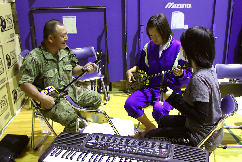 May 18, 2011; Minamisanriku, Miyagi Pref., Japan - 7:20 p.m. A soldier from Japan's Self-Defense Forces teaches Misato Abe (C) and Yayoi Kudo (R) Sanshin, an Okinawan style of playing the shamisen, at the Shizukawa High School Evacuation Center in Minamisanriku after the magnitude 9.0 Great East Japan Earthquake and Tsunami that devastated the Tohoku region of Japan on March 11, 2011.