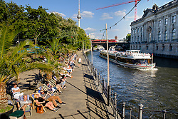 Summer afternoon view of riverside bar and cafe in Monbijoupark beside River Spree in Mitte Berlin Germany