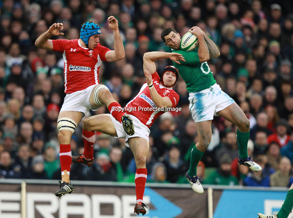 RBS Six Nations Championship, Aviva Stadium, Dublin 5/2/2012<br /> Ireland vs Wales<br /> Ireland's Rob Kearney gets the ball ahead of Justin Tipuric and Leigh Halfpenny of Wales<br /> Mandatory Credit &copy;INPHO/Billy Stickland