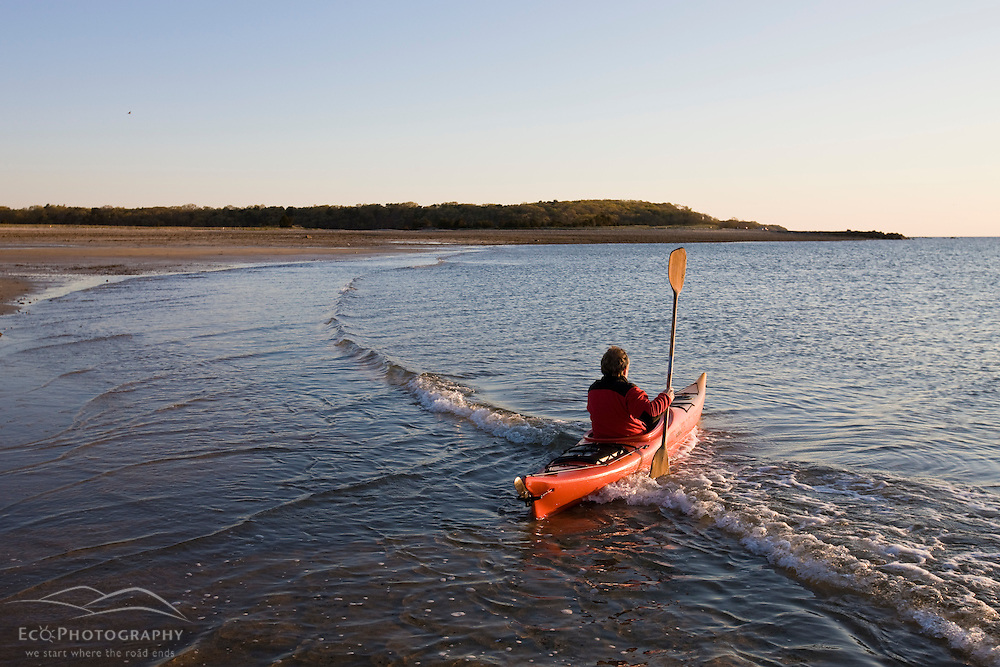 A man sea kayaking at dawn at the Shifting Lots Preserve in Plymouth, Massachusetts.  Owned by the Wildlands Trust.  Cape Cod Bay.  Near Ellisville Harbor State Park.