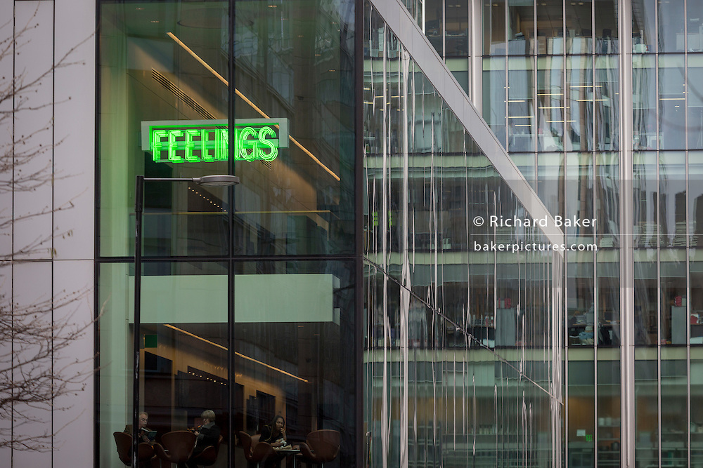 The word Feelings written in green above cafe customers, and a background of corporate office architecture, on 16th February 2017, in the City of London, England.
