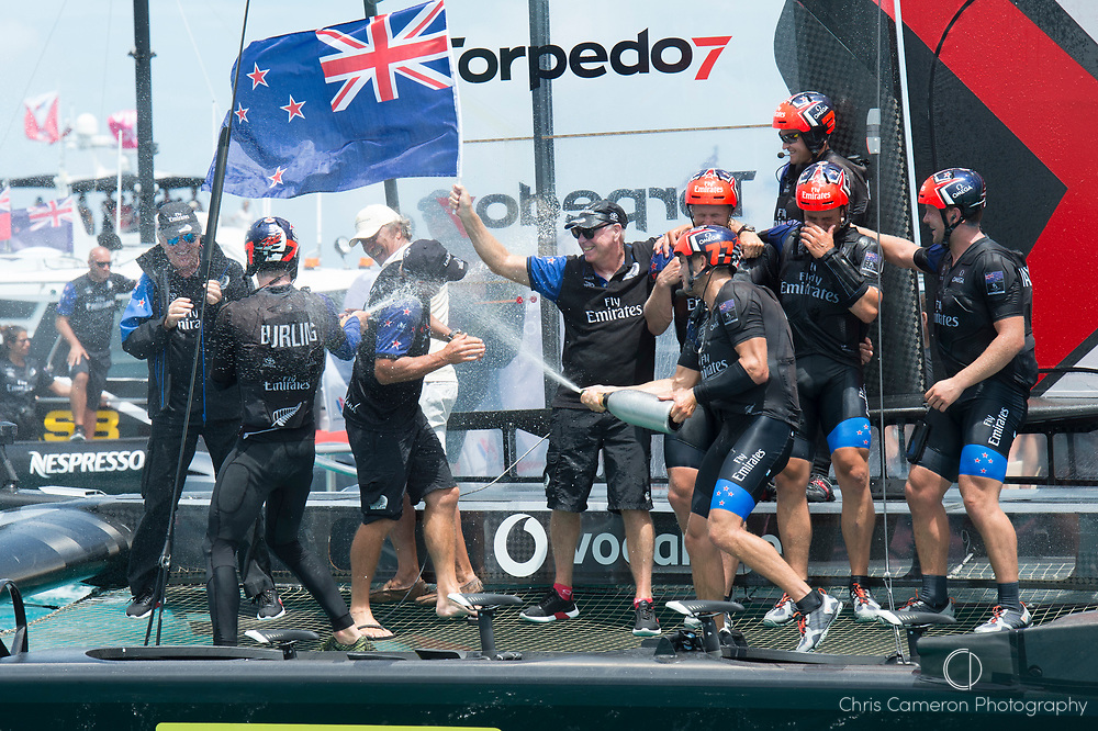 The Great Sound, Bermuda, 26th June 2017. Emirates Team New Zealand win race nine to win the America's Cup. Helmsman Peter Burling and trimmer Blair Tuke spray Grant Dalton with Moet Champagne in celebration.