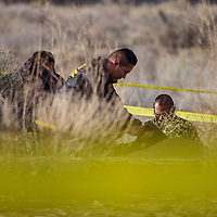 Gallup Police detective Steven Peshlakai investigates the scene where a body was found near U.S. Highway 491 in Gallup Monday.