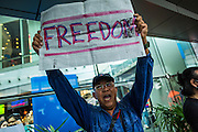 """01 JUNE 2014 - BANGKOK, THAILAND: A man screams """"freedom"""" during a protest against the Thai coup at Terminal 21, a popular shopping mall in Bangkok. The Thai army seized power in a coup that unseated a democratically elected government on May 22. Since then there have been sporadic protests against the coup. The protests Sunday were the largest in several days and seemed to be spontaneous """"flash mobs"""" that appeared at shopping centers in Bangkok and then broke up when soldiers arrived. Protest against the coup is illegal and the junta has threatened to arrest anyone who protests the coup. There was a massive security operation in Bangkok Sunday that shut down several shopping areas to prevent the protests but protestors went to malls that had no military presence.    PHOTO BY JACK KURTZ"""