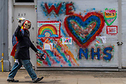 A man in an Iron Man helmet and gloves passes - We Love NHS is sprayed on the shutters of a Fulham hairdressers - The 'lockdown' continues for the Coronavirus (Covid 19) outbreak in London.
