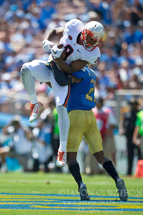 PASADENA, CA - SEPTEMBER 05:  Wide receiver Canaan Severin #9 of the Virginia Cavaliers catches a pass over defensive back Tahaan Goodman #21 of the UCLA Bruins during the first quarter at the Rose Bowl on September 5, 2015 in Pasadena, California. The UCLA Bruins defeated the Virginia Cavaliers 34-16. (Photo by Jason O. Watson/Getty Images) *** Local Caption *** Canaan Severin; Tahaan Goodman