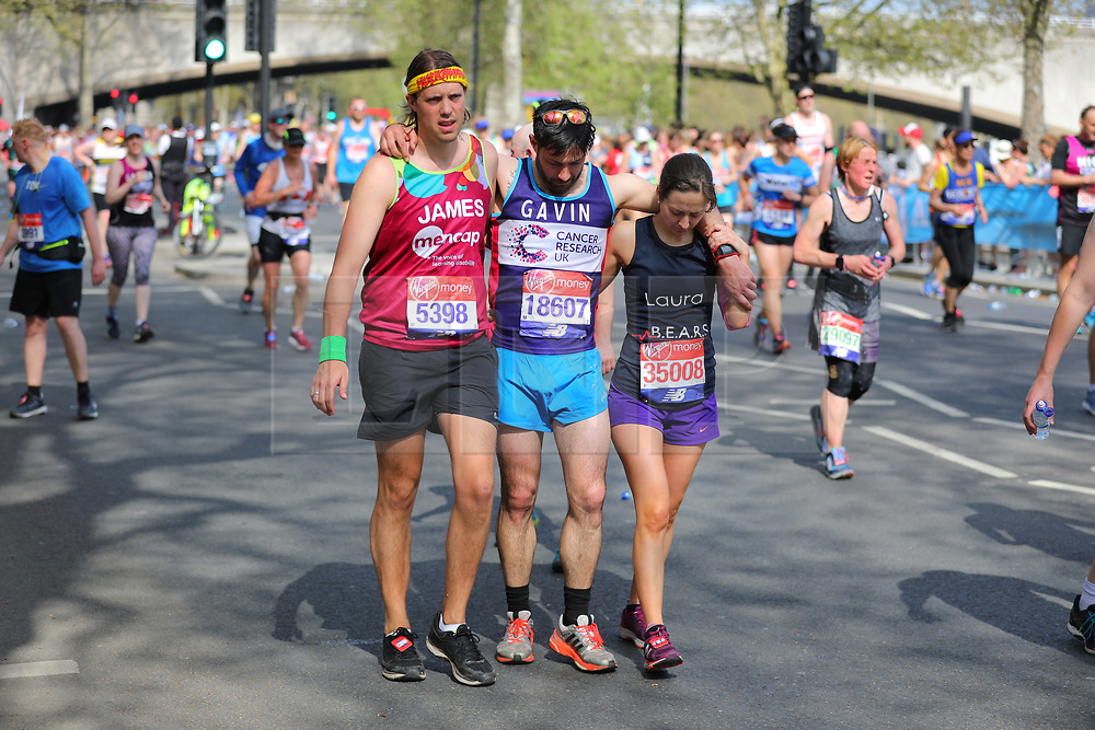 © Licensed to London News Pictures. 22/04/2018. London, UK. Two runners help a fellow runner along Embankment as record temperatures are recorded during the Virgin Money London Marathon 2018. Photo credit: Rob Pinney/LNP