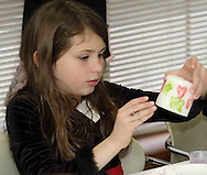 Emily Burton, 9 adds her artwork to a candle at the American Girl Tea Party, Saturday, January 27, 2007 in Waynesville's Mary L. Cook Library.