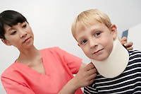 Nurse assisting boy wearing neck brace in hospital