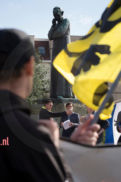 nederland, Enschede 01okt2017 een spreker krijgt de microfoon voorgehouden door Constant Kusters bij de NVU demonstratie  terwijl zij  worden gadegeslagen door het standbeeld van Alphons Ariens op het Ariensplein in Enschede . Bij de demonstratie van de Nedelandse Volks Unie in Enschede. Ongeveer dertig leden / sympatisanten van de NVU  demonstreerden zondag in de buurt van het station van Enschede. Er was een grote politiemacht op de been om de demo rustig te laten verlopen. Er waren geen linkse tegendemonstranten en na twee uur was de demo afgelopen.