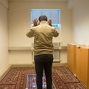 Mohamed prays is a student of Philosophy at the University of Iceland. He organises with a group of migrants, some newly arrived in the country, an annual event that unites people of different religions praying together.