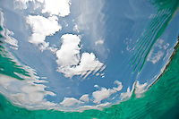 Bright blue sky, white clouds viewed from beneath the ocean surface.