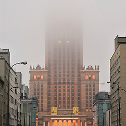 Streets of Warsaw with the communist Palac Kultury i Nauki building under the fog, Poland, Europe.