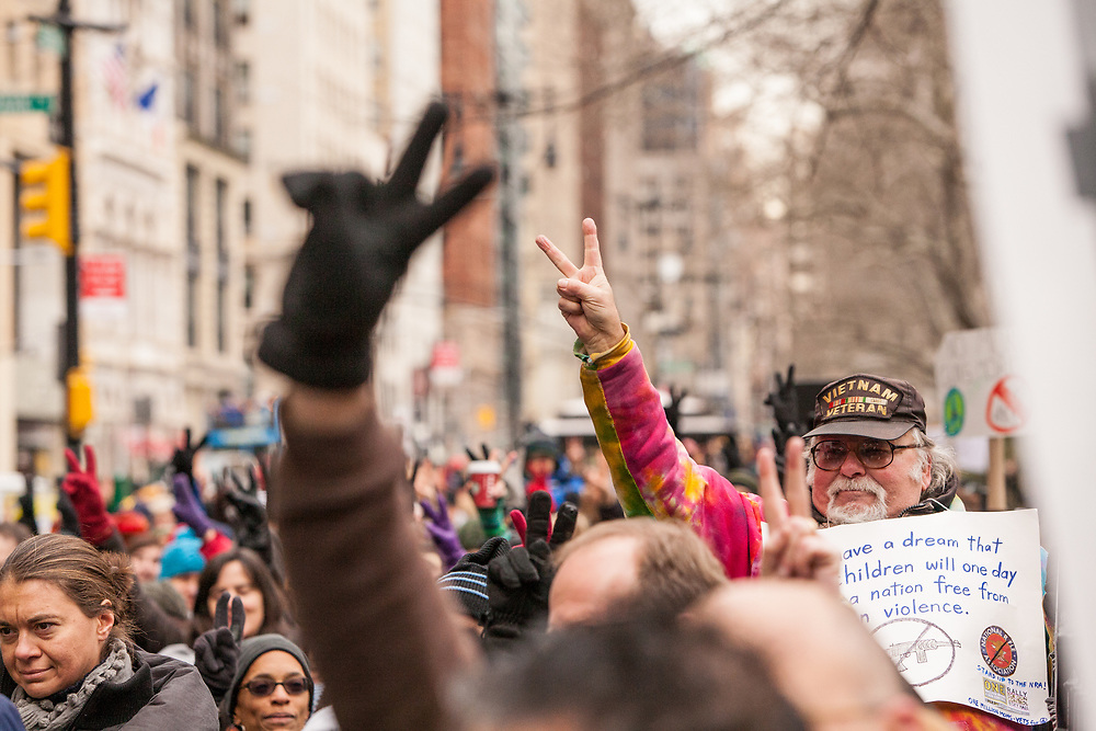 A number of the crowd, including a Vietnam veteran, wave peace signs.