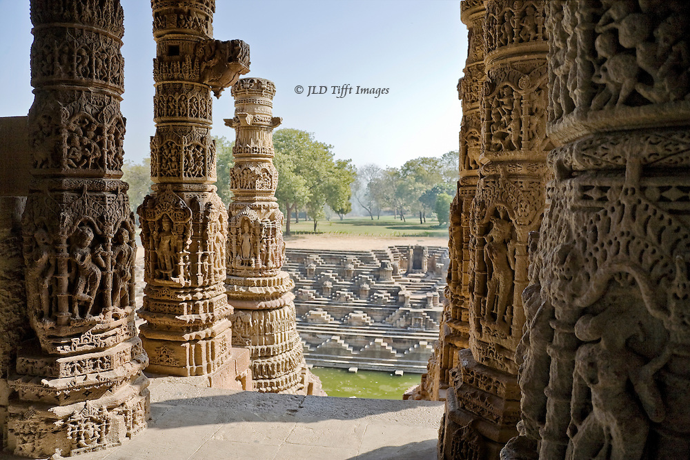 Modhera, 11th century Sun temple colonnade overlooking water-filled tank and steps, orchard beyond.  The all-over carvings of the columns are in Jain style.