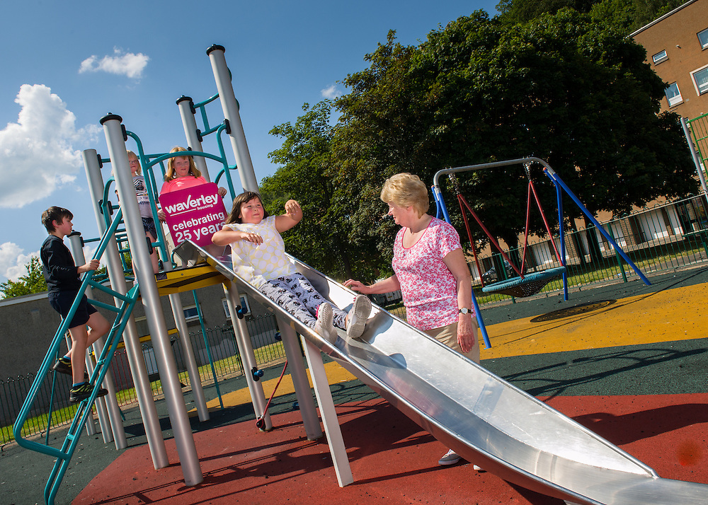Waverley Housing Community Star Award winner, Judith Cleghorn, in the Jubilee Play Park, along with local children playing on the slide.