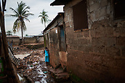 A girl walks through mud and garbage in Kroo Bay, a slum area in in Freetown, Sierra Leone on June 8, 2017. Malaria and poverty are intimately connected with those least able to afford preventative measures and medical treatment feeling the impact of the disease.