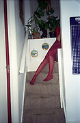 A woman wearing pink tights sitting on the stairs, UK 2000's
