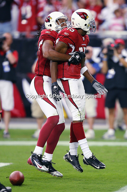 GLENDALE, AZ - OCTOBER 12: Wide receiver Steve Breaston #15 of the Arizona Cardinals gets a celebratory lift from Larry Fitzgerald #11 of the Cardinals after Breaston catches an 11 yard touchdown pass during the game against the Dallas Cowboys at University of Phoenix Stadium on October 12, 2008 in Glendale, Arizona. The Cardinals defeated the Cowboys 30-24. ©Paul Anthony Spinelli *** Local Caption *** Steve Breaston;Larry Fitzgerald