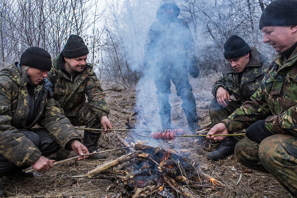 ARTEMIVSK, UKRAINE - FEBRUARY 15: Ukrainian soldiers cook sausage over a fire along the road leading to the embattled town of Debaltseve on February 15, 2015 outside Artemivsk, Ukraine. A ceasefire scheduled to go into effect at midnight was reportedly observed along most of the front, save for near the embattled town of Debaltseve. (Photo by Brendan Hoffman/Getty Images) *** Local Caption ***