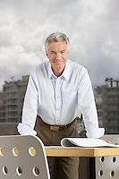 Business man leaning on desk portrait