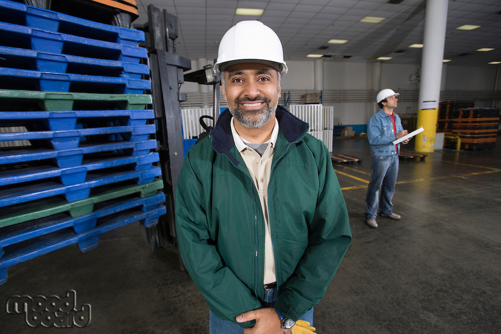 Cheerful man standing in factory wearing hart hat