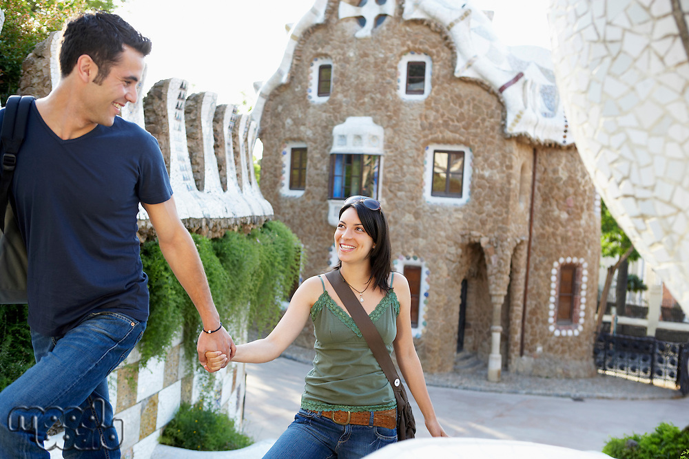 Young couple sightseeing holding hands