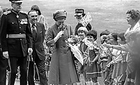 At the start of her Silver Jubilee Visit to N Ireland Queen Elizabeth II is greeted by local school children after her arrival by helicopter at Hillsborough Castle, her official residence whilst visiting the Province. Immediately behind her is Roy Mason, Secretary of State for N Ireland. 197708100074R<br /> <br /> Copyright Image from Victor Patterson, 54 Dorchester Park, <br /> Belfast, UK, BT9 6RJ<br /> <br /> t1: +44 28 9066 1296 (from Rep of Ireland 048 9066 1296)<br /> t2: +44 28 9002 2446 (from Rep of Ireland 048 9002 2446)<br /> m: +44 7802 353836<br /> <br /> e: victorpatterson@me.com<br /> www.victorpatterson.com<br /> <br /> Please see my Terms and Conditions of Use at www.victorpatterson.com. It is IMPORTANT that you familiarise yourself with them.<br /> <br /> Images used on the Internet must be visibly watermarked i.e. © Victor Patterson<br /> within the body of the image and copyright metadata must not be deleted. Images <br /> used on the Internet have a size restriction of 4kbs and will be chargeable at current<br />  NUJ rates unless agreed otherwise.<br /> <br /> This image is only available for the use of the download recipient i.e. television station, newspaper, magazine, book publisher, etc, and must not be passed on to any third <br /> party. It is also downloaded on condition that each and every usage is notified within 7 days to victorpatterson@me.com<br /> <br /> The right of Victor Patterson to be identified as the author is asserted in accordance with The Copyright Designs And Patents Act (1988). All moral rights are asserted.