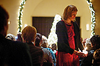 Deneen Davis helps light candles for attendees of Hospice of North Idaho's 30th annual Tree Lighting ceremony held Monday at the Jacklin Arts and Cultural Center in Post Falls.