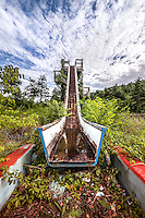 An old overgrown waterslide at an abandoned amusement park.