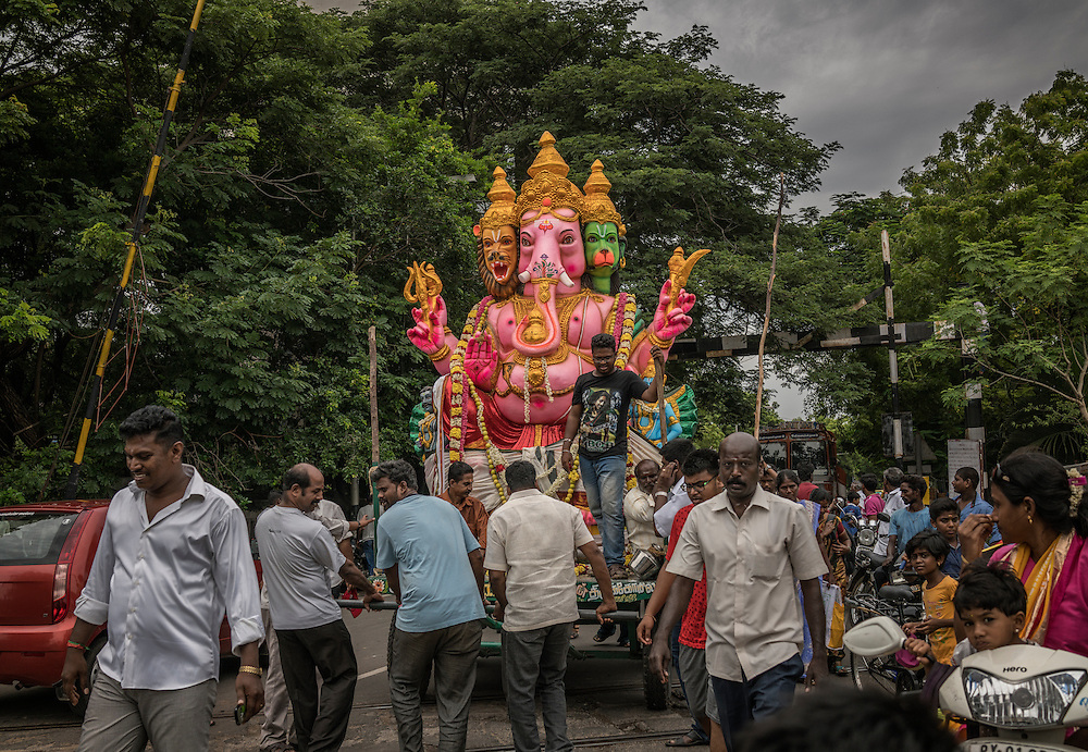 Local men navigate all kinds of obstacles to deliver a large Lord Ganesha statue from the center of Pondicherry to the port area, where it will be loaded on a boat and taken out to sea to be thrown into Bay of Bengal and symbolically back to nature.  Pondicherry, India.