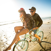 Young couple riding a cruiser bike on the beach in Encinitas, CA.
